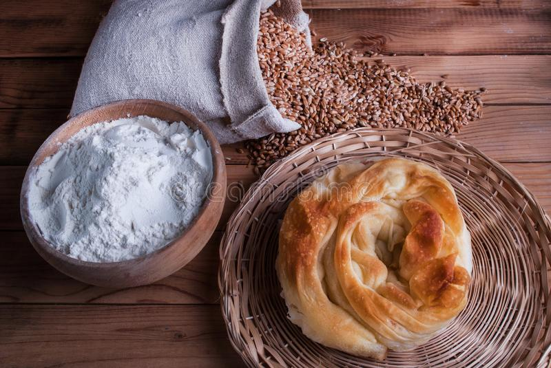 Freshly homemade pie with cheese and flour in bowl and wheat grains in bag on wooden table royalty free stock photography