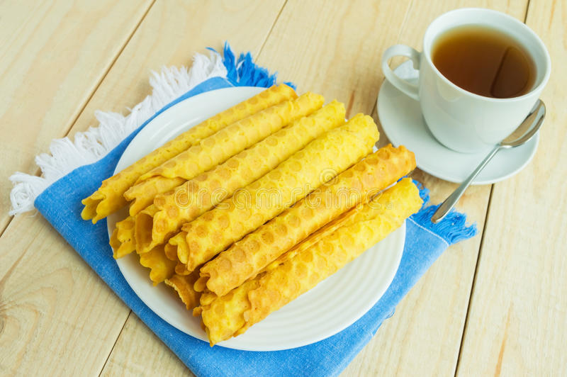 Freshly honey waffles rolled up into tubes. On a blue napkin royalty free stock photos