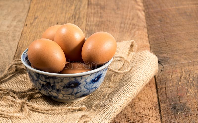 Freshly laid organic eggs in bowl on wooden bench. Easter background with brown organic eggs arranged in a bowl on burlap sack on rustic wooden table stock images