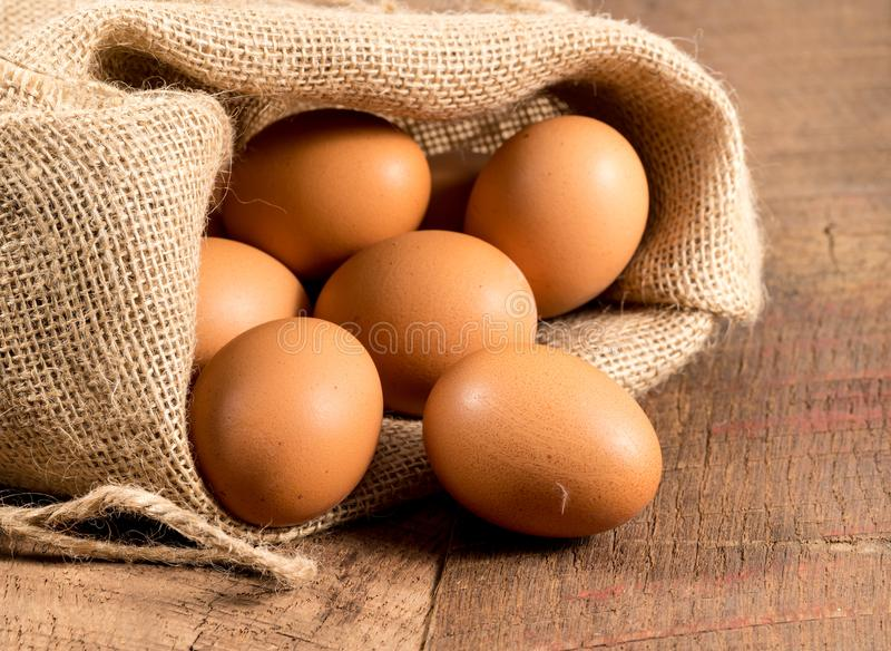 Freshly laid organic eggs in burlap sack on wood. Easter background with brown organic eggs arranged inside a burlap sack on rustic wooden table stock image