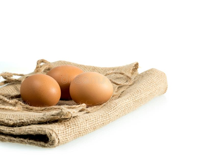 Freshly laid organic eggs on wooden bench. Easter background with brown organic eggs arranged on burlap sack and isolated against white background stock photo
