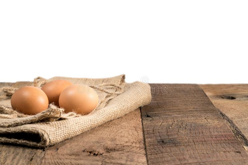Freshly laid organic eggs on wooden bench. Easter background with brown organic eggs arranged on burlap sack on rustic wooden table with background royalty free stock image