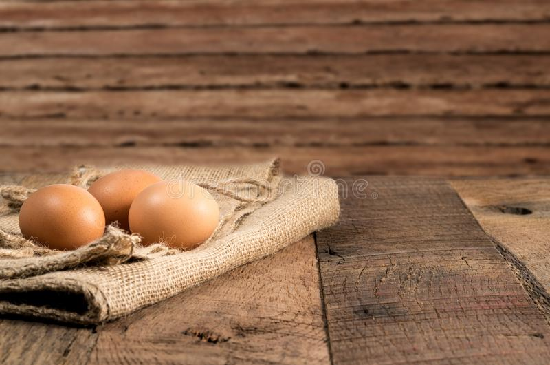 Freshly laid organic eggs on wooden bench. Easter background with brown organic eggs arranged on burlap sack on rustic wooden table royalty free stock images