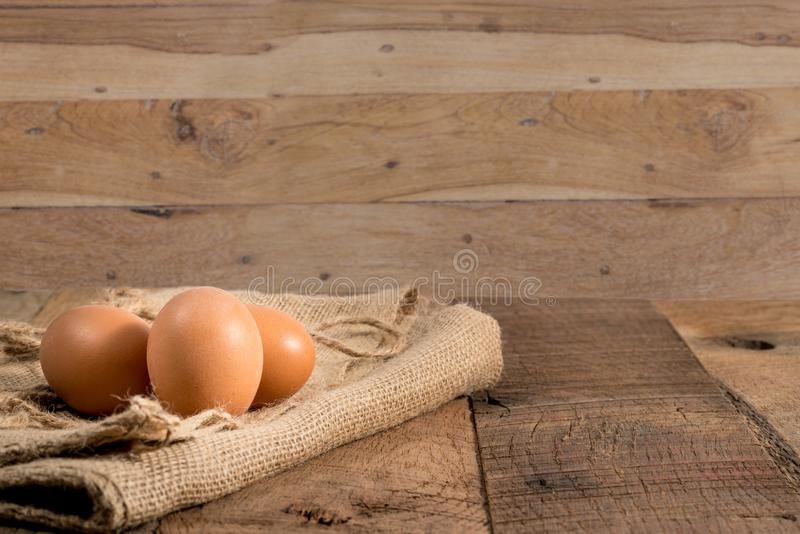 Freshly laid organic eggs on wooden bench. Easter background with brown organic eggs arranged on burlap sack on rustic wooden table stock photography