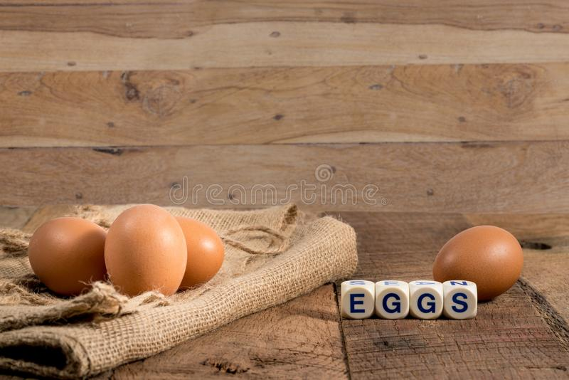 Freshly laid organic eggs on wooden bench. Easter background with brown organic eggs arranged on burlap sack on rustic wooden table royalty free stock photos