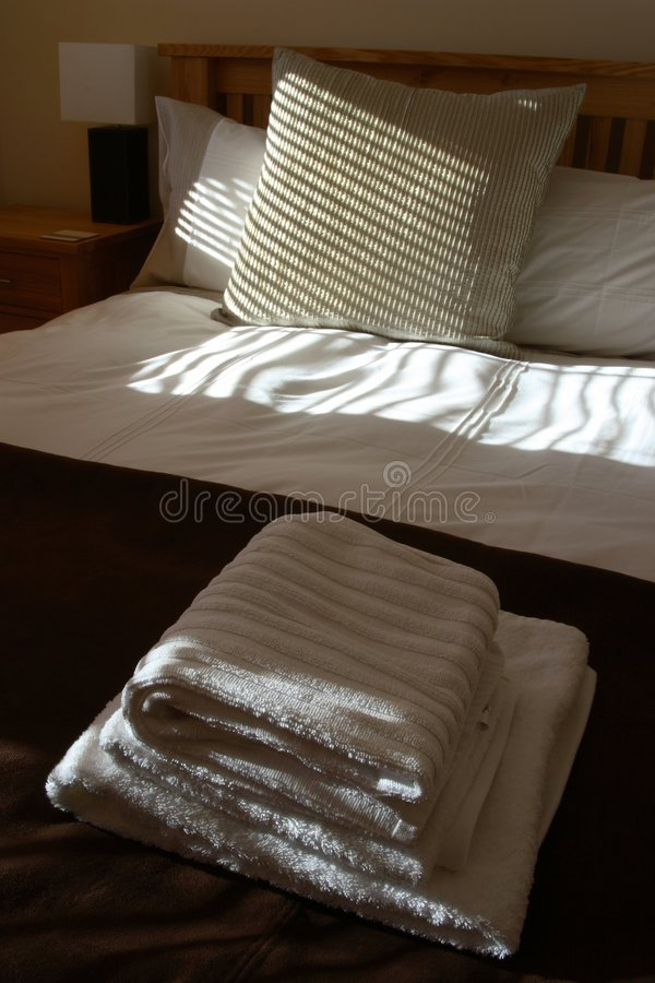 Freshly made bed in a smart hotel room royalty free stock images