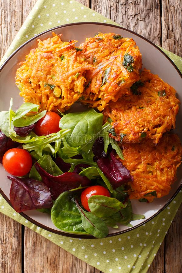 Freshly made crispy fritters from sweet potato and fresh vegetable salad close-up. Vertical top view stock photo