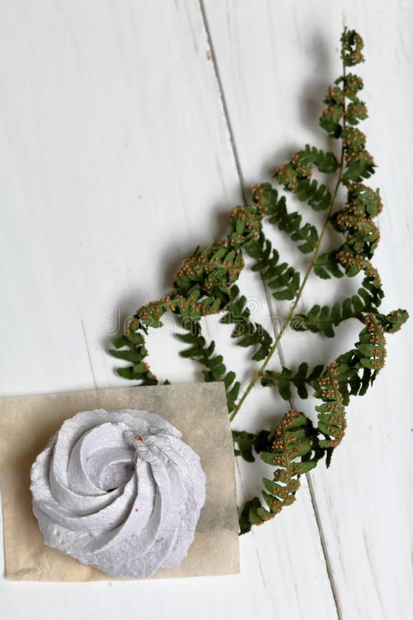 Freshly made lavender marshmallows on white painted boards.  Decorated with a dry leaf of fern. View from above stock photo