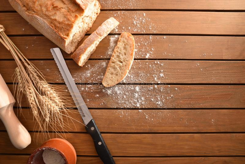 Freshly made loaf of bread cut on wooden table top stock image