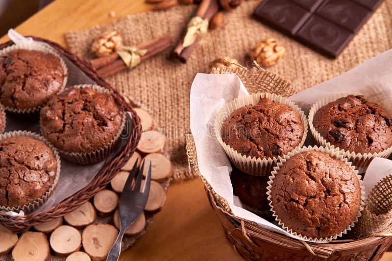 Freshly made muffins in a basket with walnuts, almonds, dark chocolat e. there is a fork nearby. Freshly made muffins in a basket with walnuts, almonds, dark stock photos