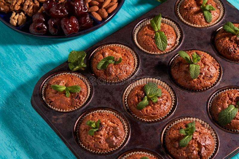 Freshly made muffins with mint served to the table with dates almonds and walnuts stock photography