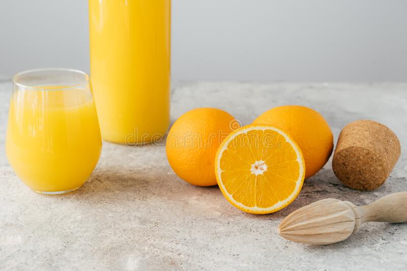 Freshly made orange juice containing vitamin C, sliced oranges, wooden cork and squeezer. Process of making fruit drink. Healthy. Beverage stock images