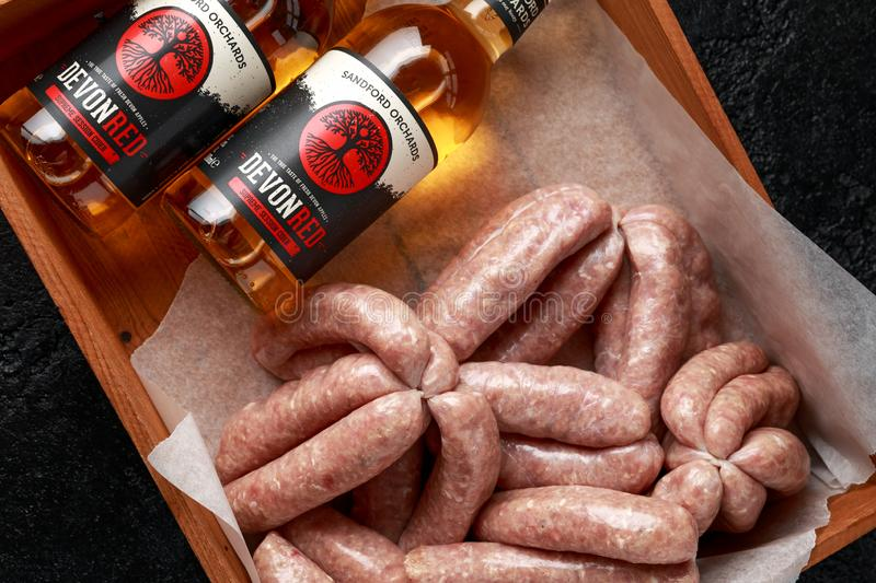 Freshly made raw butchers sausages in skins with Sanford orchards apple cider, Devon, United Kingdom, March 20, 2019. stock photos
