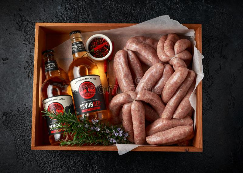 Freshly made raw butchers sausages in skins with Sanford orchards apple cider, Devon, United Kingdom, March 20, 2019. royalty free stock photo