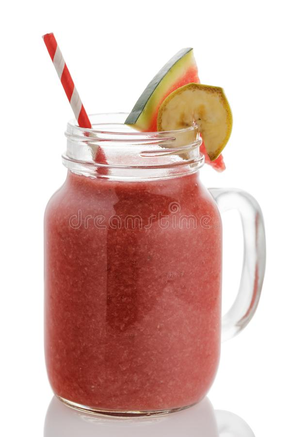 Freshly made smoothies from slices of watermelon and banana. In a glass jar on a white background stock photo