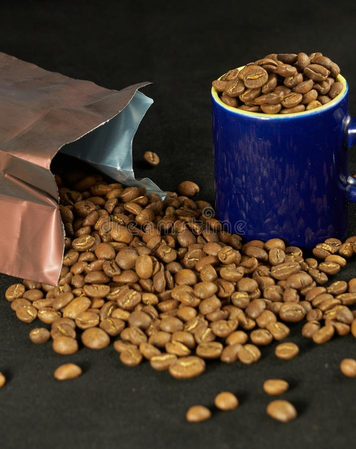 A freshly opened coffee pack with the beans strewn, next to a cup of full blue coffee. The objects are on a black background, illuminated with a soft light stock images