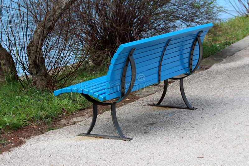 Freshly painted blue wooden public bench with black metal supports mounted on paved sidewalk in front of grass and dense. Vegetation on warm spring day stock image