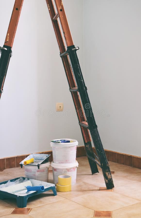 Freshly painted light blue room with painting equipments at home and ladder. Painting accessories are in an empty room. stock images