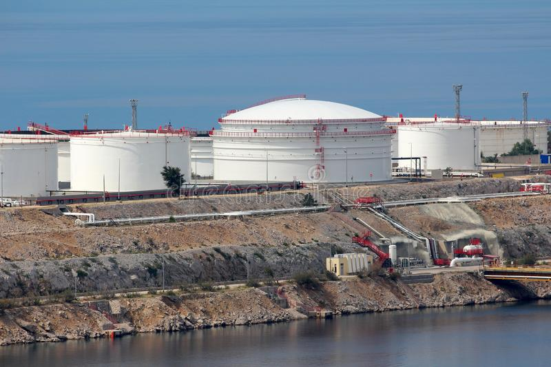 Freshly painted new large industrial white metal oil refinery tanks on top of rocky sea shore connected with metal pipes to pier. Freshly painted new large stock photo