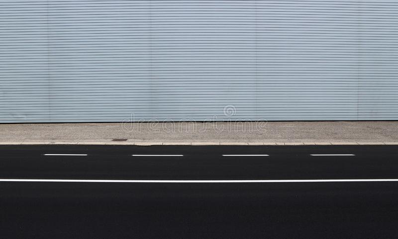 Freshly paved road, a concrete sidewalk and a modern metallic cladding wall on behind. Background for copy space stock photo