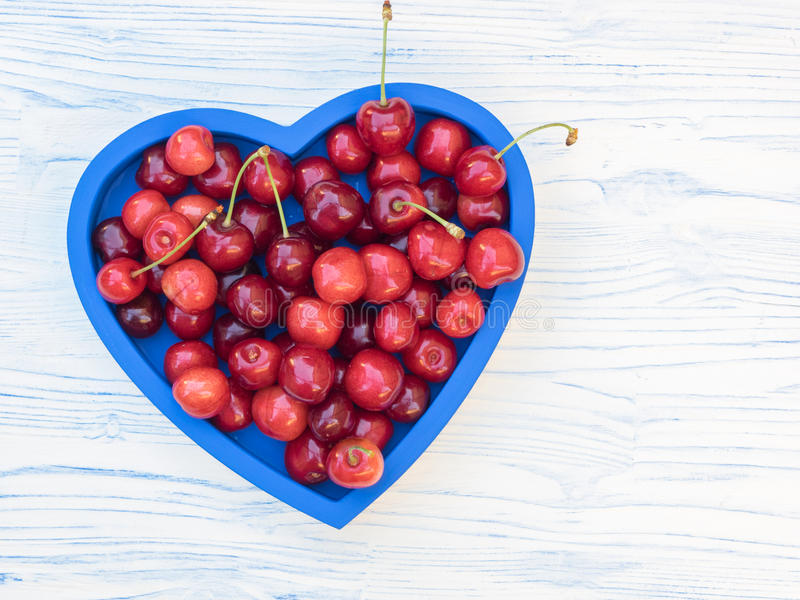 Freshly picked cherries on a blue heart shaped tray. Freshly picked cherries on a blue heart-shaped tray, set on a white and blue wooden board royalty free stock photo