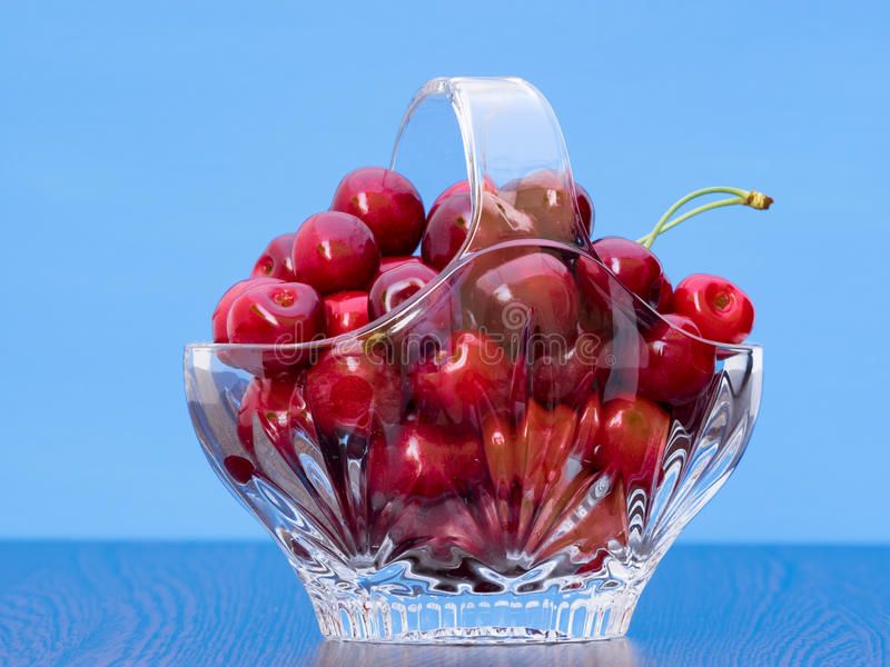 Freshly picked cherries in a crystal basket. With blue background stock photo