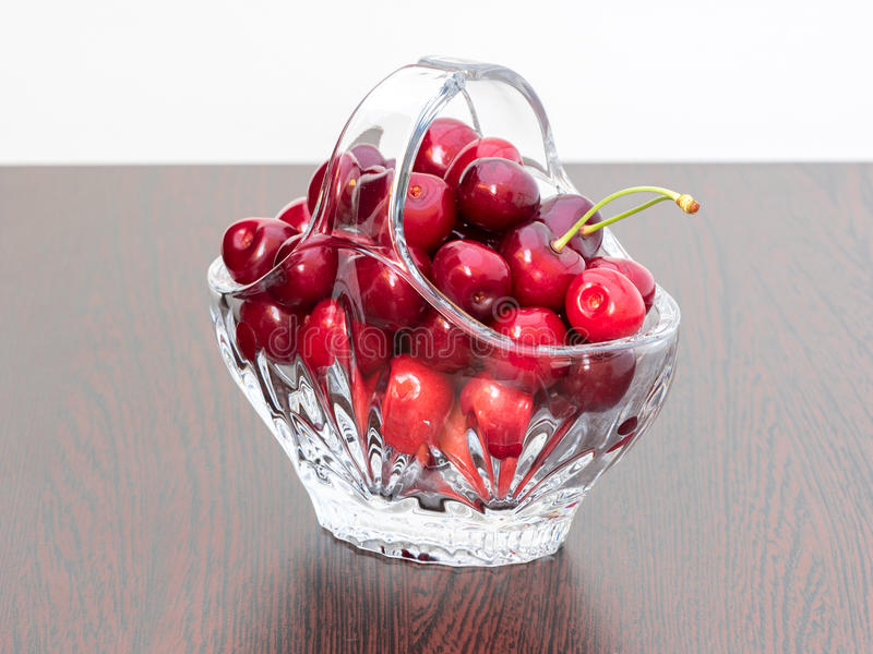 Freshly picked cherries in a crystal basket. Set on a dark brown wooden board, with white background royalty free stock images