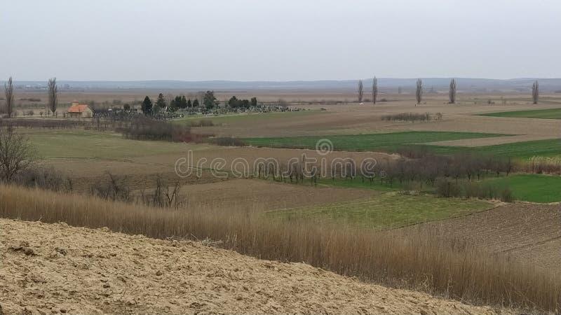 Freshly plowed field. Arable land with fertile soil for planting wheat. Rural landscape in Serbia, Balkans, namely Fruska Gora. From Sremska Mitrovica. Furrows stock images
