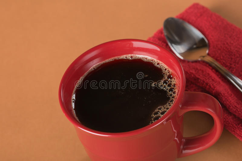 Freshly poured black coffee in a red mug stock photo