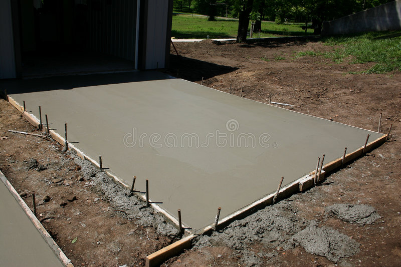 Freshly Poured Concrete Pad. A freshly poured concrete pad with forms and stakes still in place royalty free stock photography