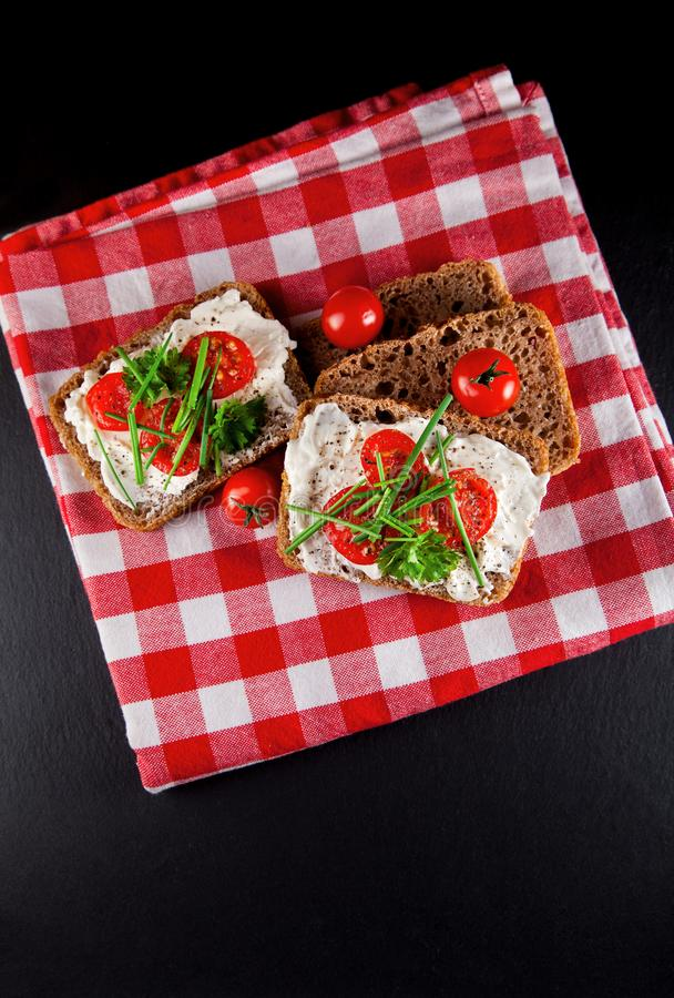 Freshly prepared bread slices with cream cheese, tomatoes and chives stock images