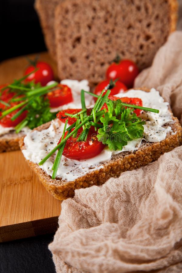 Freshly prepared bread slices with cream cheese, tomatoes and chives stock photography