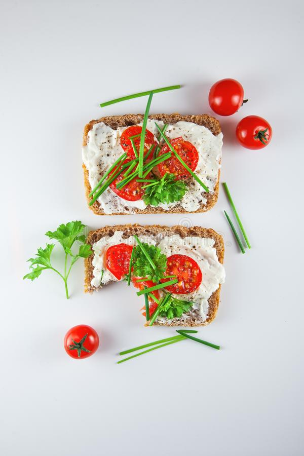 Freshly prepared bread slices with cream cheese, tomatoes and chives stock photo