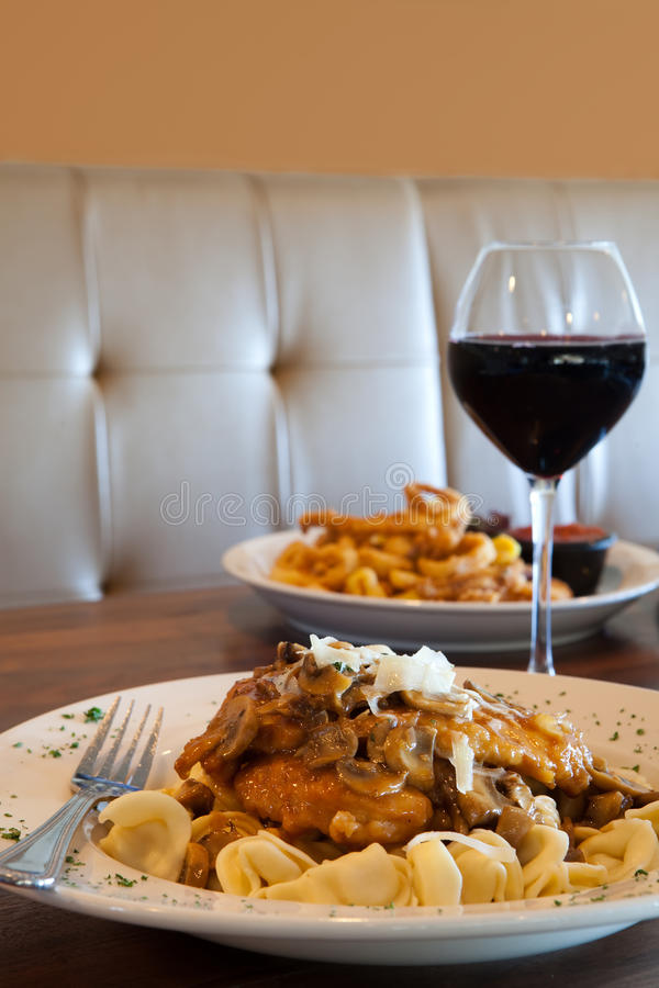 Freshly Prepared Chicken Marsala dinner. With a glass of wine royalty free stock photo
