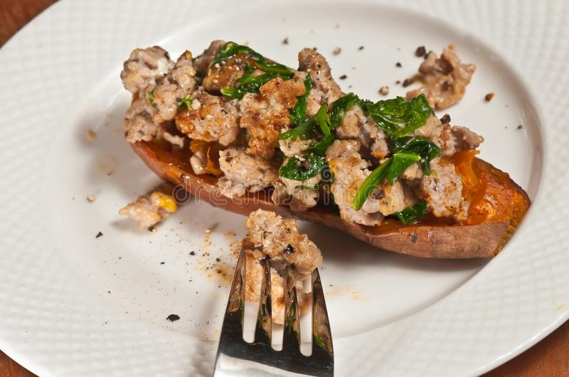 Freshly prepared, homemade, sweet potato skin filled with italian sausage and spinish stock images