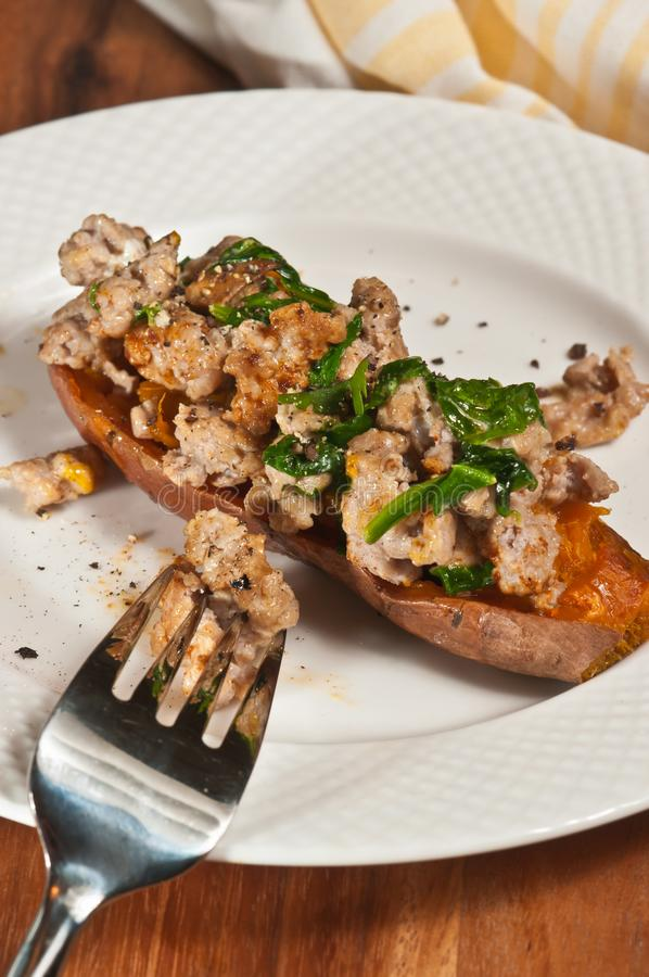 Freshly prepared, homemade, sweet potato skin filled with italian sausage and wilted spinach. Top view, close distance of freshly prepared, homemade, sweet royalty free stock photography
