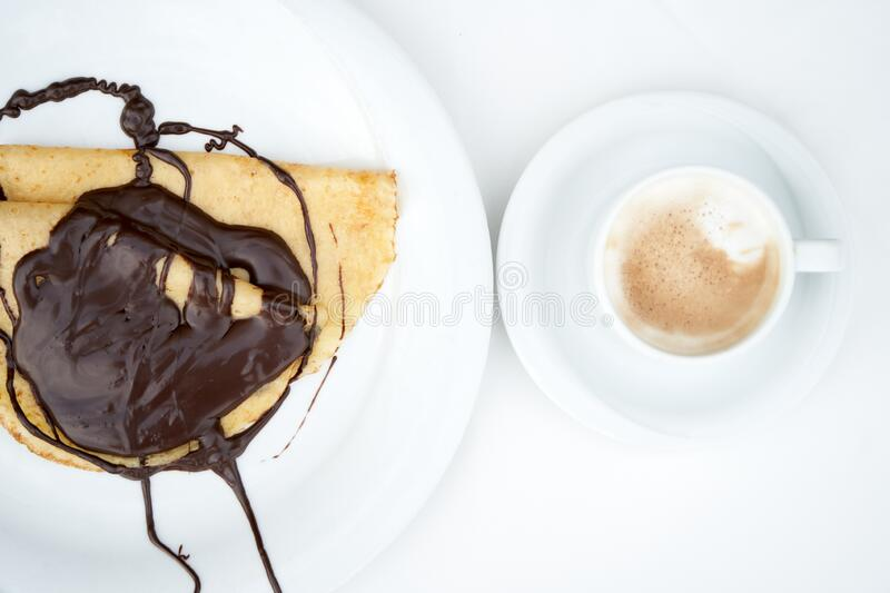 Freshly prepared pancakes, poured with chocolate on a white plate with a fork, with a cup of coffee, on a table stock photo