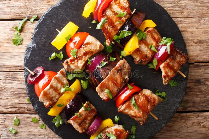 Freshly prepared pork skewers with vegetables close-up on a slat stock images