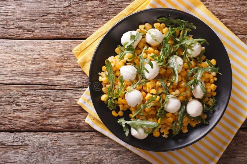freshly prepared salad of corn, baby mozzarella and arugula closeup. Horizontal top view royalty free stock photo