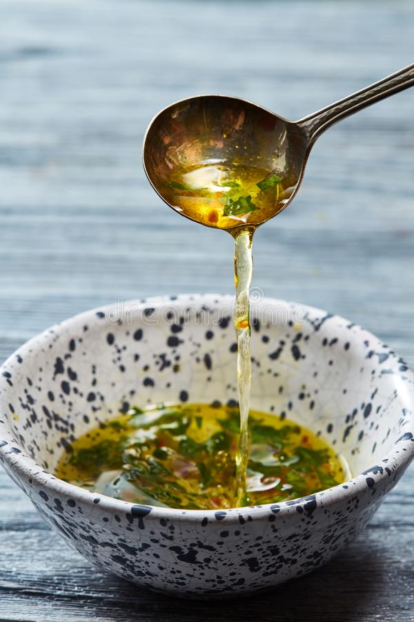Homemade salad dressing with olive oil, vinegar, greens and spices pour from a spoon into a bowl on a gray wooden table. stock images
