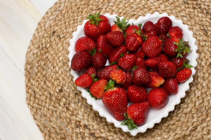 FRESHLY RIPE STRAWBERRIES SERVED ON A HEART WHITE PLATE WITH A J stock photo