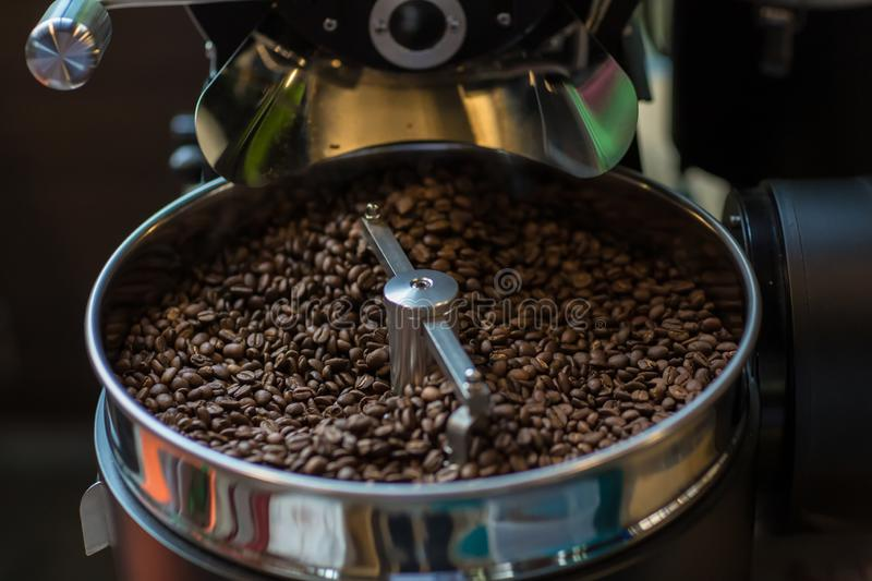 Freshly roasted aromatic coffee beans in a modern coffee roasting machine. Fresh Coffee Beans - Freshly roasted spinning cooler pr stock photography