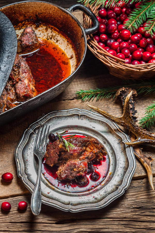 Freshly roasted venison with cranberry sauce and rosemary stock photography