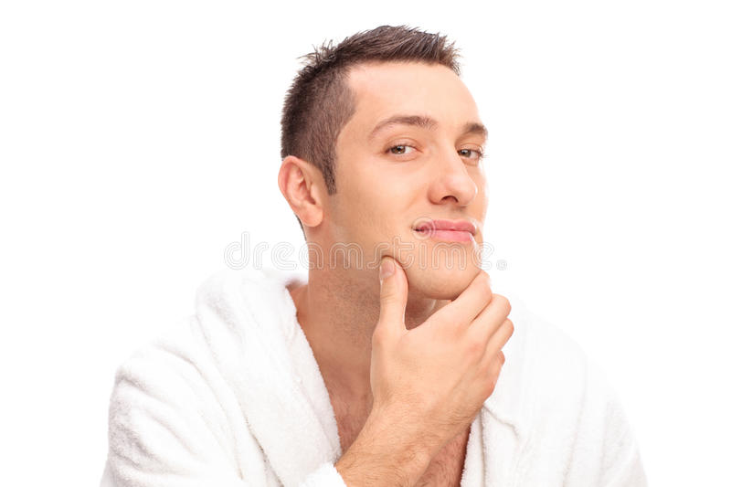 Freshly shaved young man in a white bathrobe. Looking at the camera isolated on white background royalty free stock images