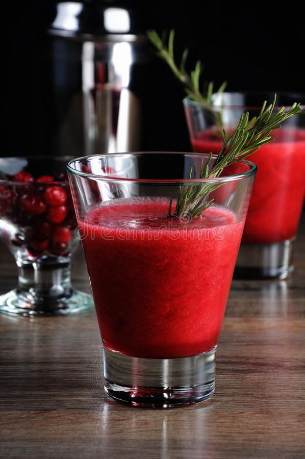 Freshly squeezed cranberry smoothie. Freshly made cranberry smoothie with a sprig of rosemary stock images