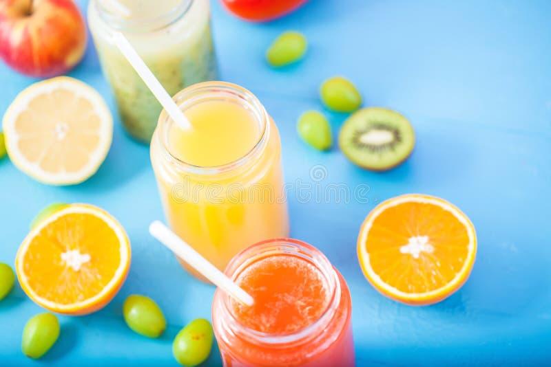 Freshly squeezed fruit juice, smoothies yellow orange green blue banana lemon apple orange kiwi grape strawberry on bright blue ba stock images