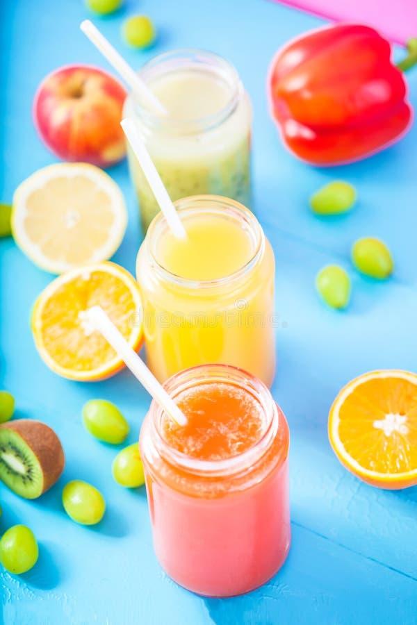 Freshly squeezed fruit juice, smoothies yellow orange green blue banana lemon apple orange kiwi grape strawberry on bright blue ba royalty free stock images
