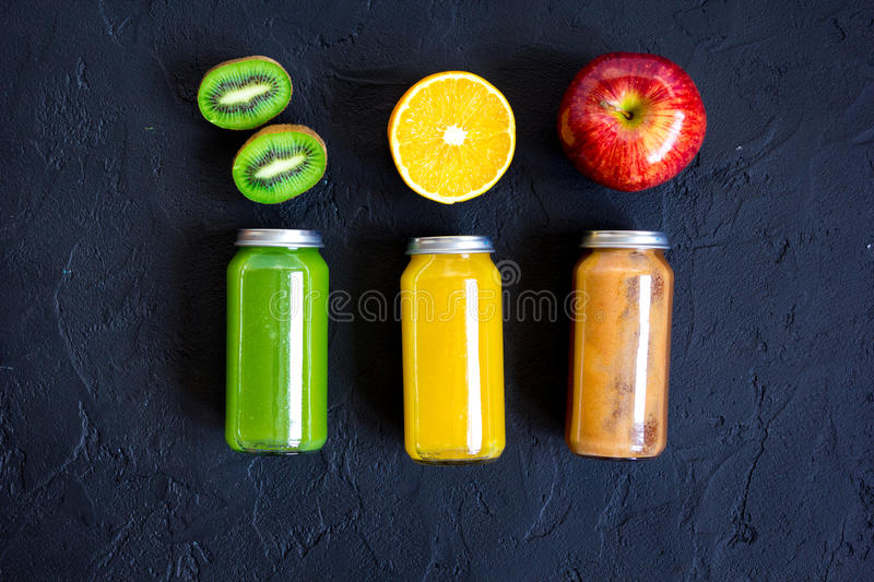 Freshly squeezed juices for detox on dark background top view.  stock images
