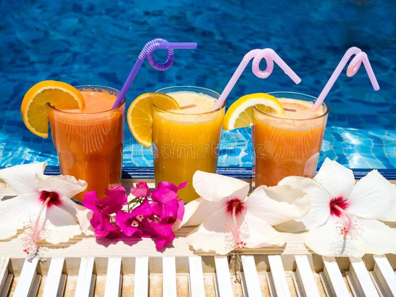 Freshly squeezed natural juice and pool. Three glasses of vitamin freshly squeezed natural juice with fruit slices and straws on the pool edge at the resort on stock image