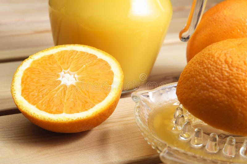 Freshly Squeezed Orange Juice. A jug of orange juice with whole and cut oranges and an orange squeezer on a wooden table royalty free stock photo
